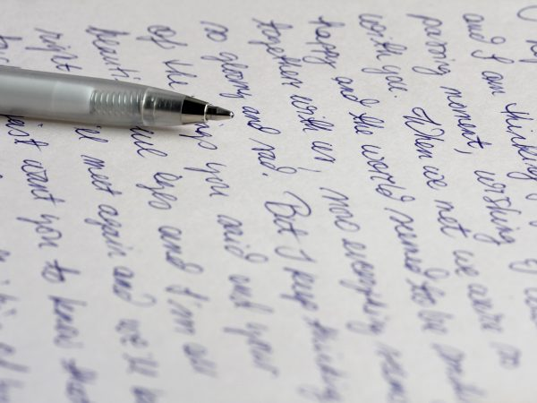 A handwritten letter with a silver ballpoint pen.